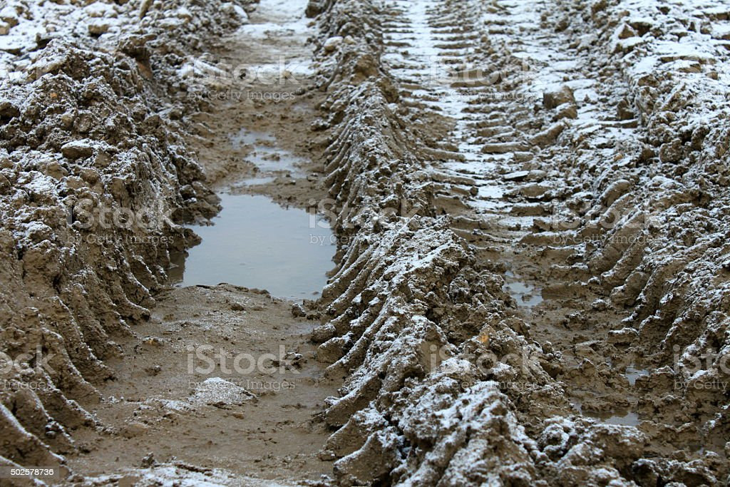 Wheel tracks on dirt and snow, impassable section of road stock photo