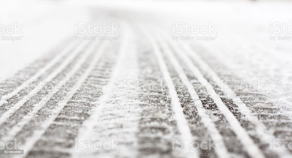 Wheel tracks on the road covered with snow stock photo