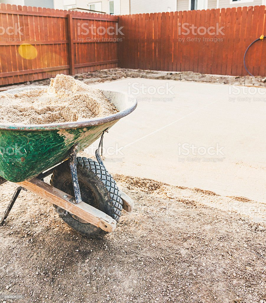 Wheelbarrow filled with sand for backyard patio construction stock photo
