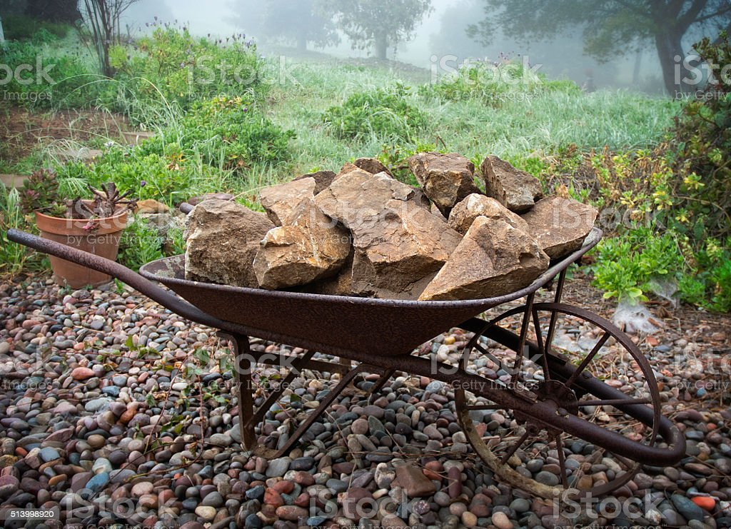 Wheelbarrow Full Of Brown Rocks Outdoors In Garden On Pebbles stock photo