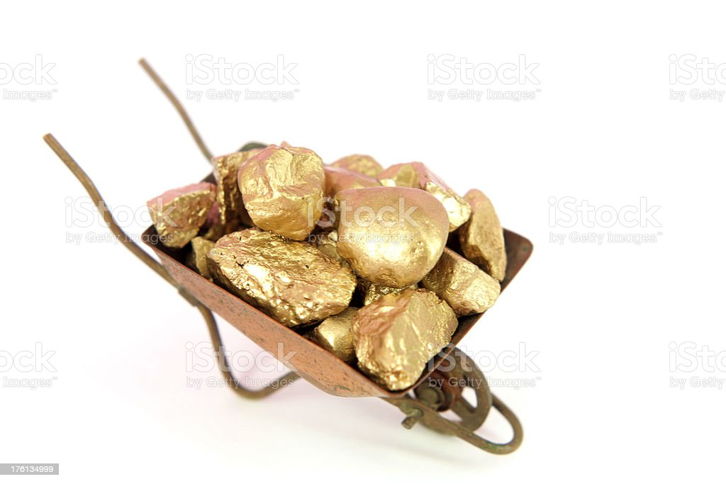 Wheelbarrow full of gold nuggets royalty-free stock photo