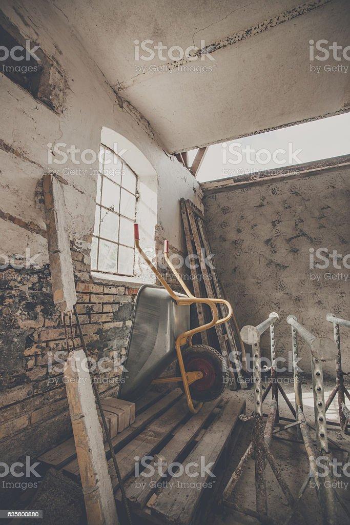 Wheelbarrow in a warn barn stock photo