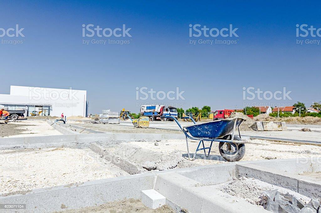 Wheelbarrow is at building site beside newly roadside stones stock photo
