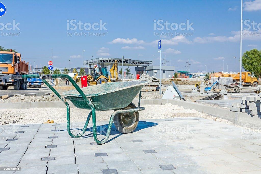 Wheelbarrow is on construction site. Landscape transform into ur stock photo