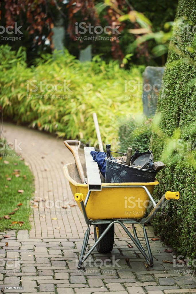 Wheelbarrow with instruments in a garden royalty-free stock photo