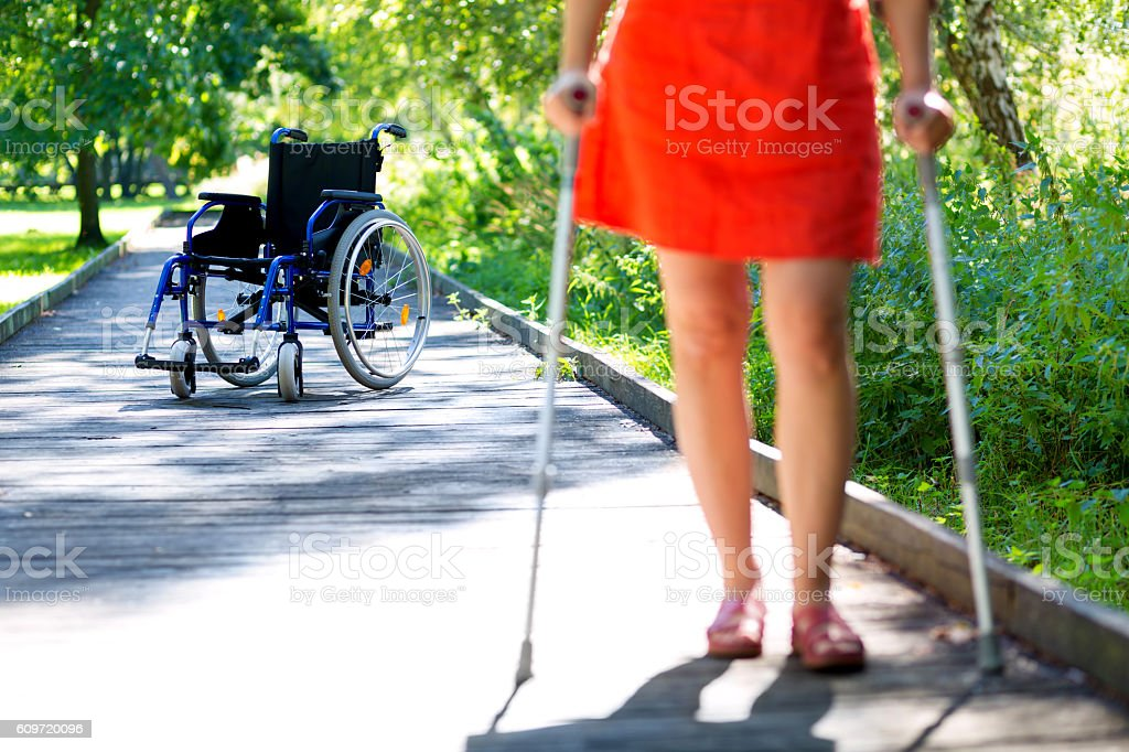 wheelchair and woman practicing walking on crutches stock photo