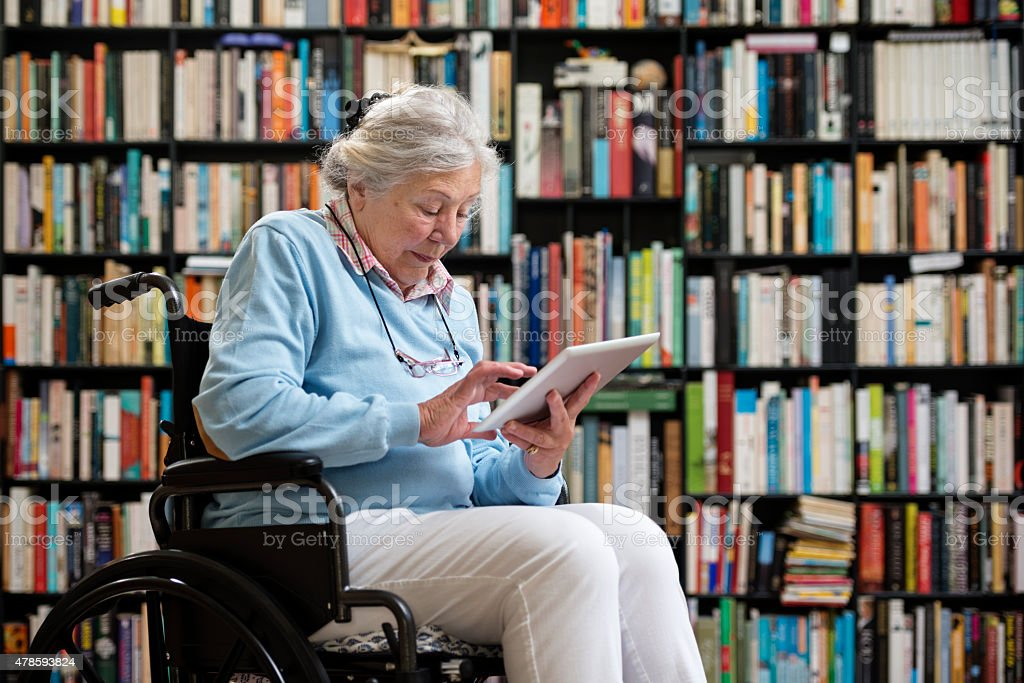 Wheelchair Bound Senior Woman Using a Digital Tablet stock photo