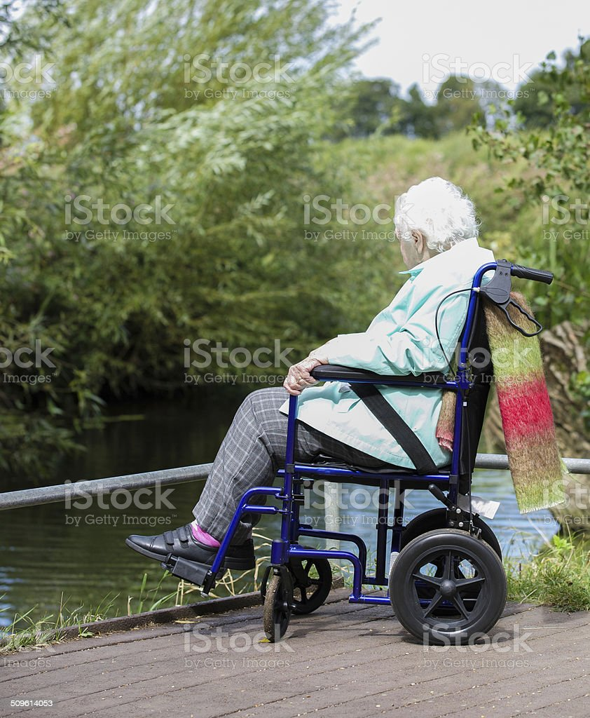 Wheelchair bound woman next to river on disabled access platform stock photo