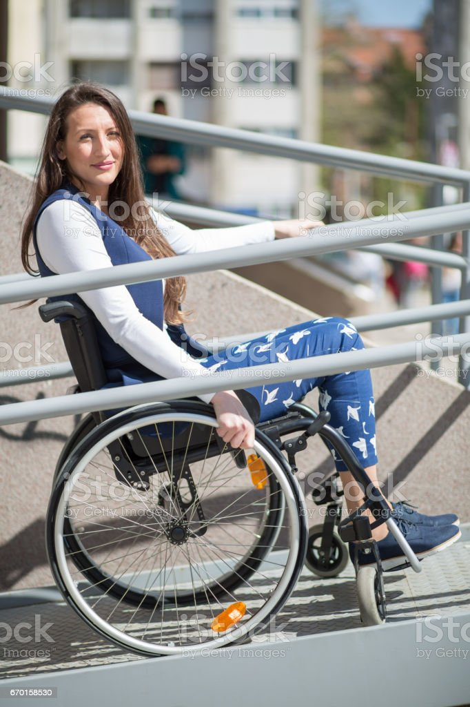 wheelchair ramp help for a young woman stock photo