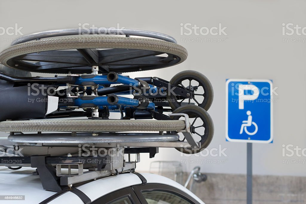 Wheelchair transported on a car's roof. stock photo
