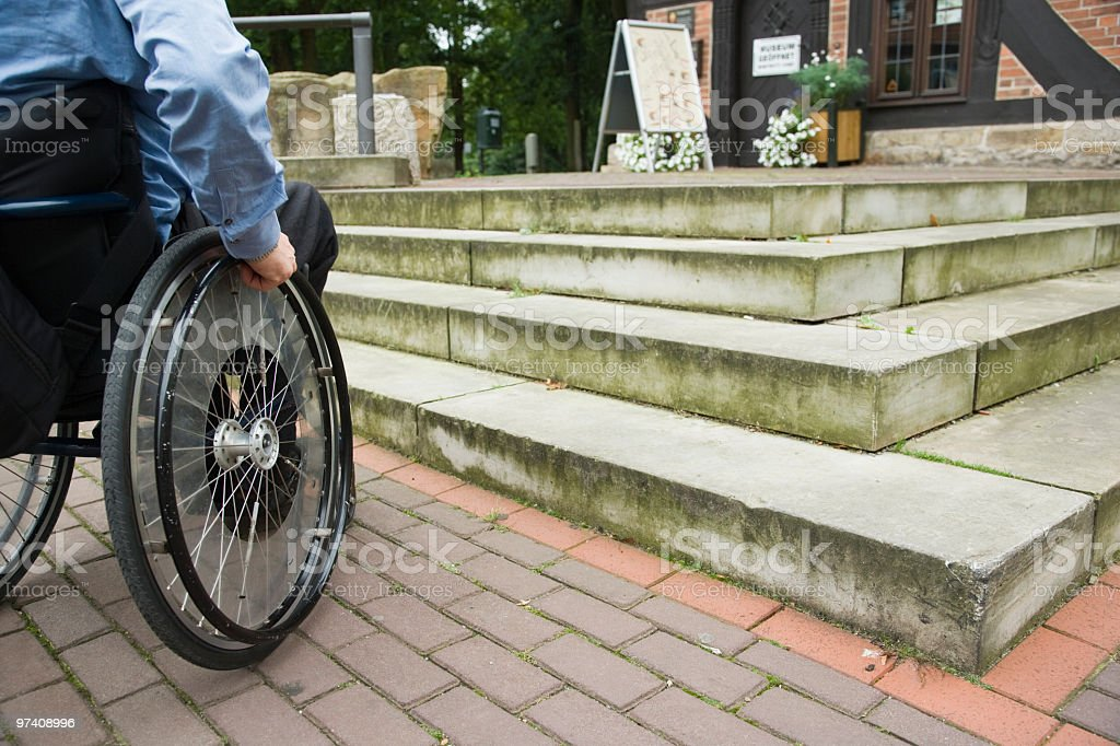 Wheelchair user in front of staircase barrier (XXL) stock photo
