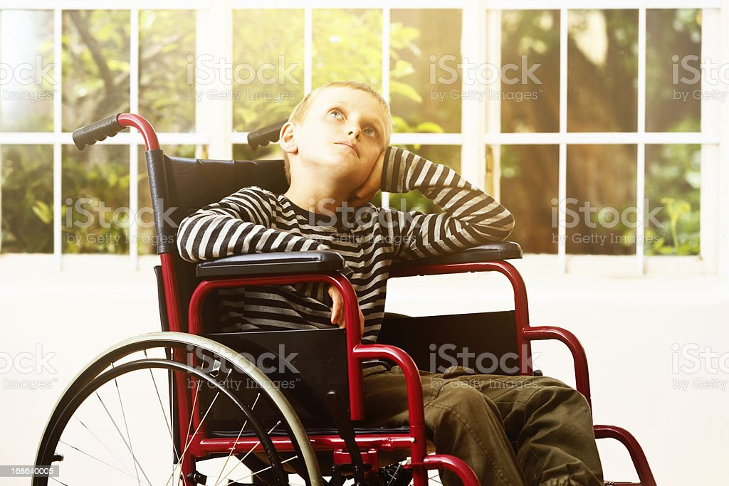Wheelchair-bound little boy looks upwards, tired, bored and frustrated stock photo