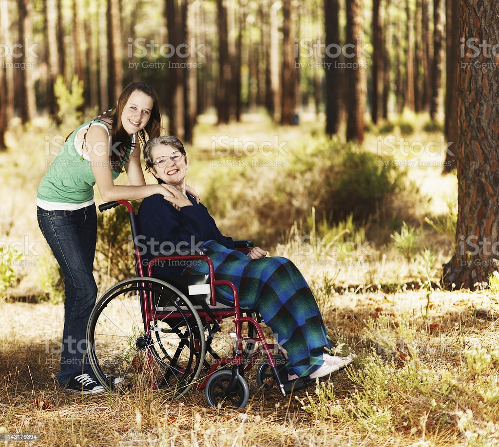 Wheelchair-bound old lady and young companion enjoy exploring forest royalty-free stock photo