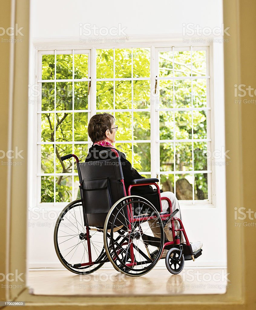 Wheelchair-bound woman looks longingly at garden she cannot reach royalty-free stock photo
