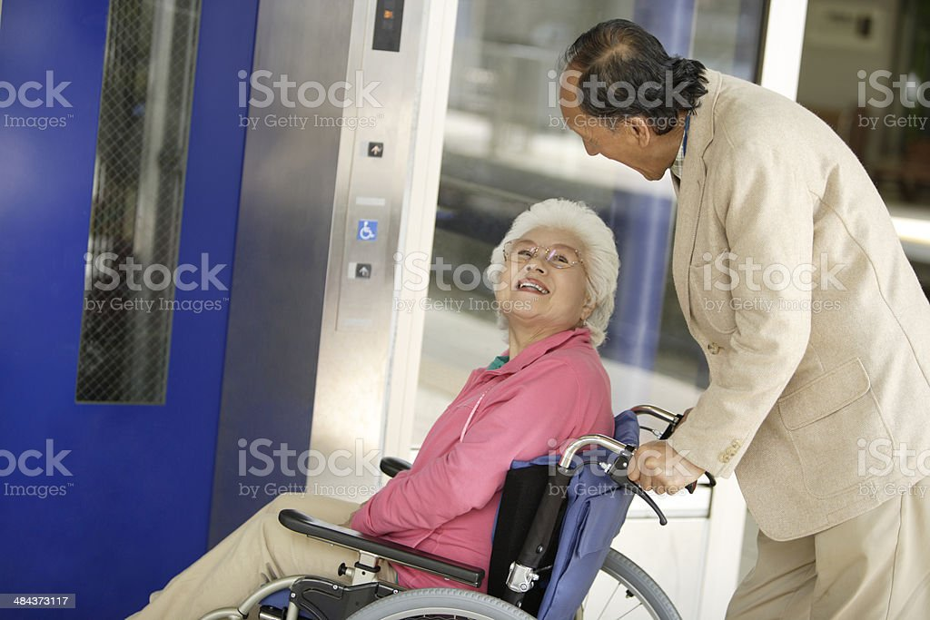 Wheelchaired wife and husband using an elevator stock photo