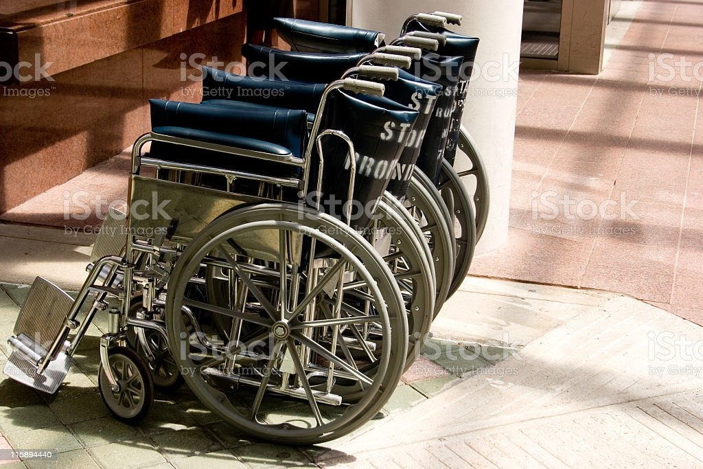 Wheelchairs in a row. Hospital queue. No people. stock photo