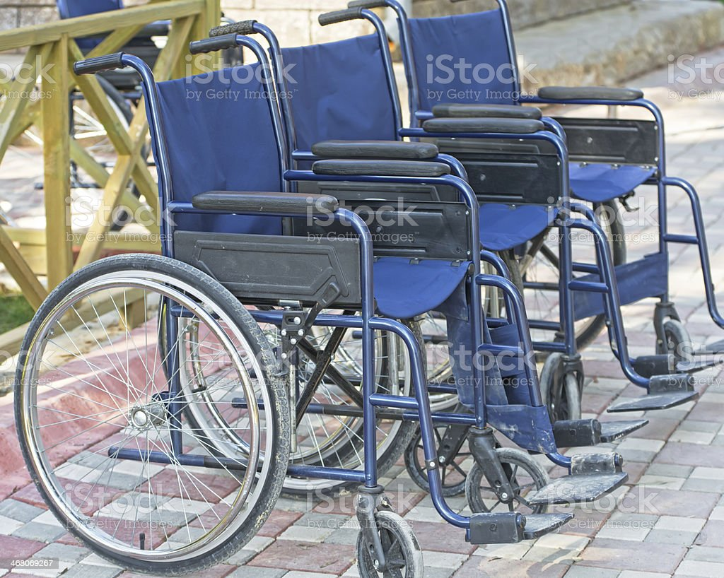 Wheelchairs parked on the side of a road stock photo