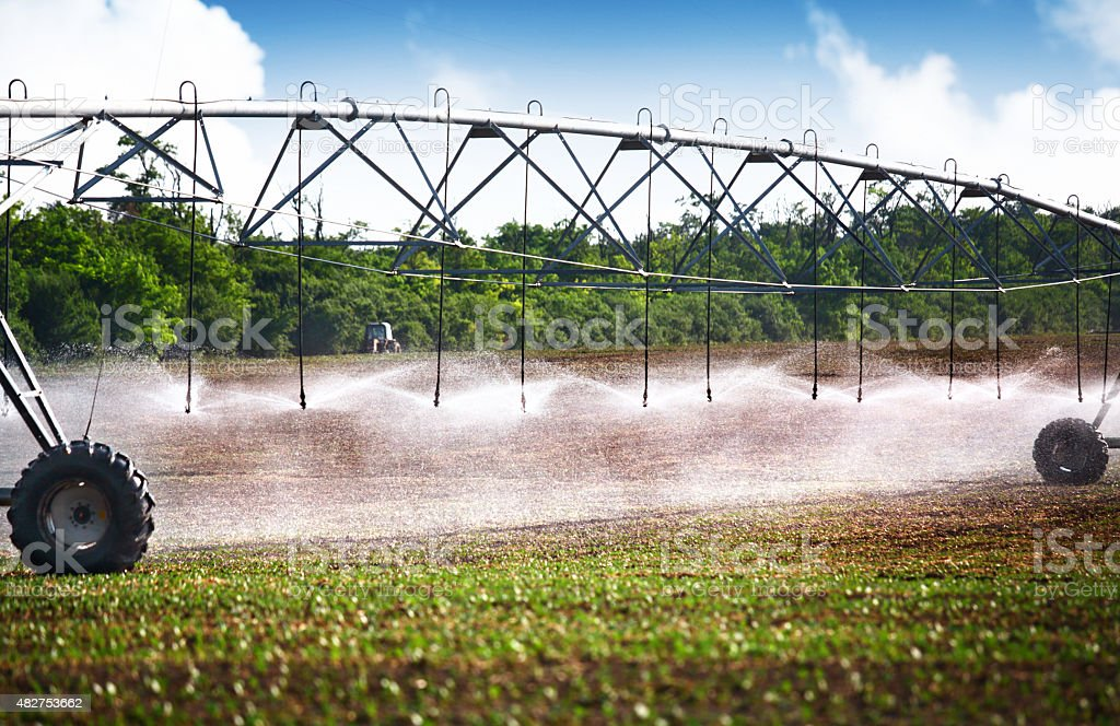 Wheeled irrigation on agricultural soil. stock photo