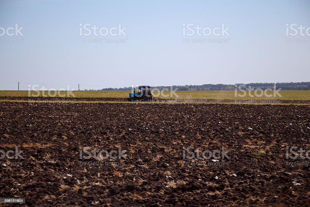 Wheeled tractor plowing arable land stock photo