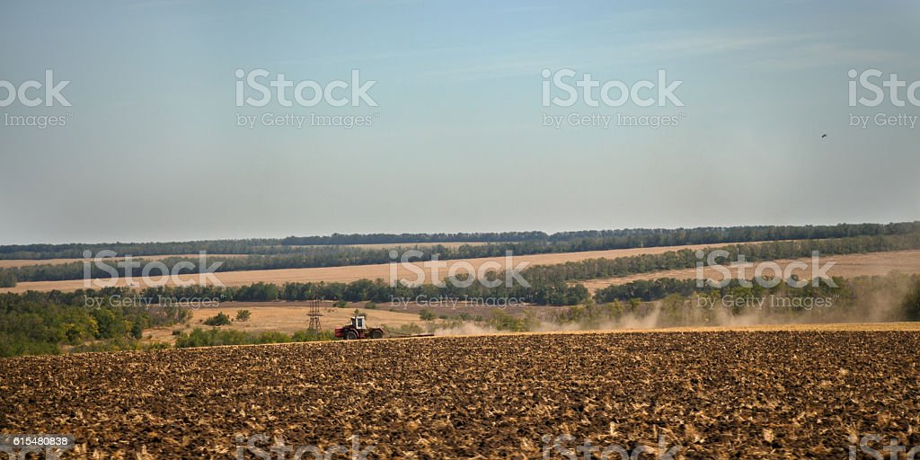 Wheeled tractor plows arable land stock photo