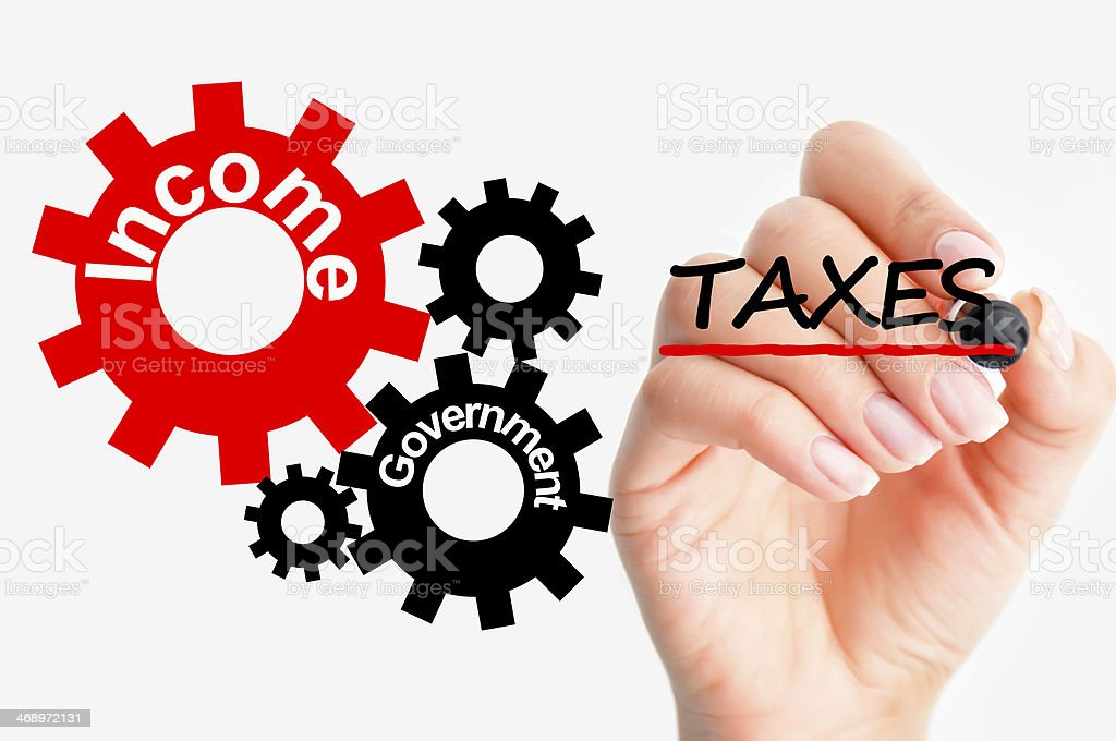 Wheels depicting the tax system with hand writing on a glass stock photo