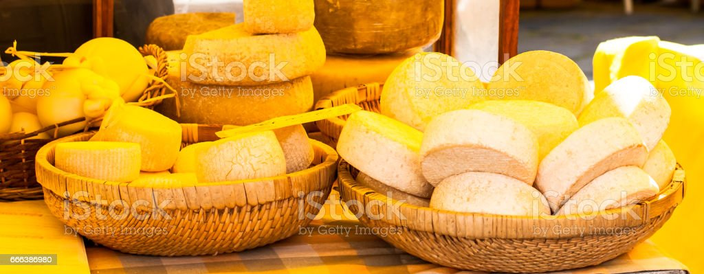 wheels of cheese and dairy products in wicker baskets stock photo