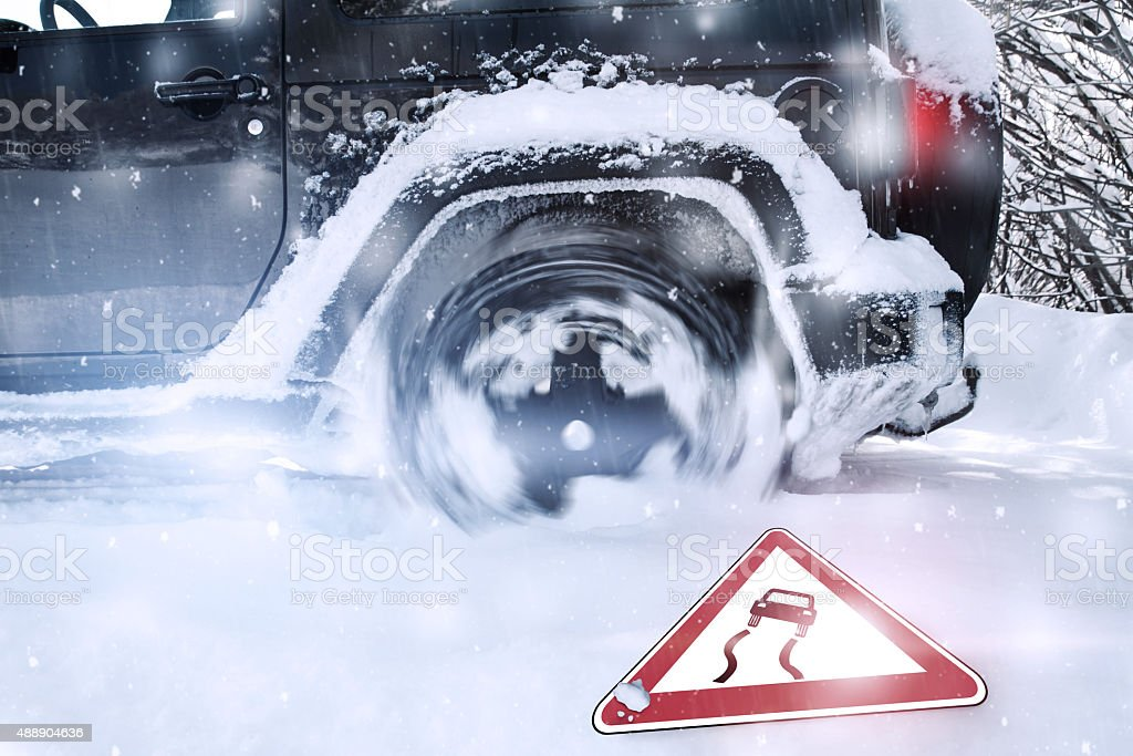 Wheelspinning of car tires at wintertime stock photo
