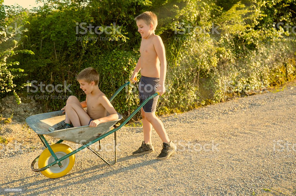 whellbarrow race funny kid in the countryside stock photo
