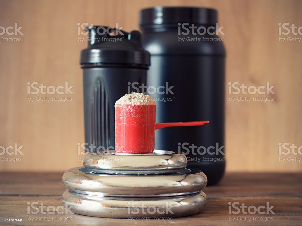 Whey protein powder in a red cup stock photo