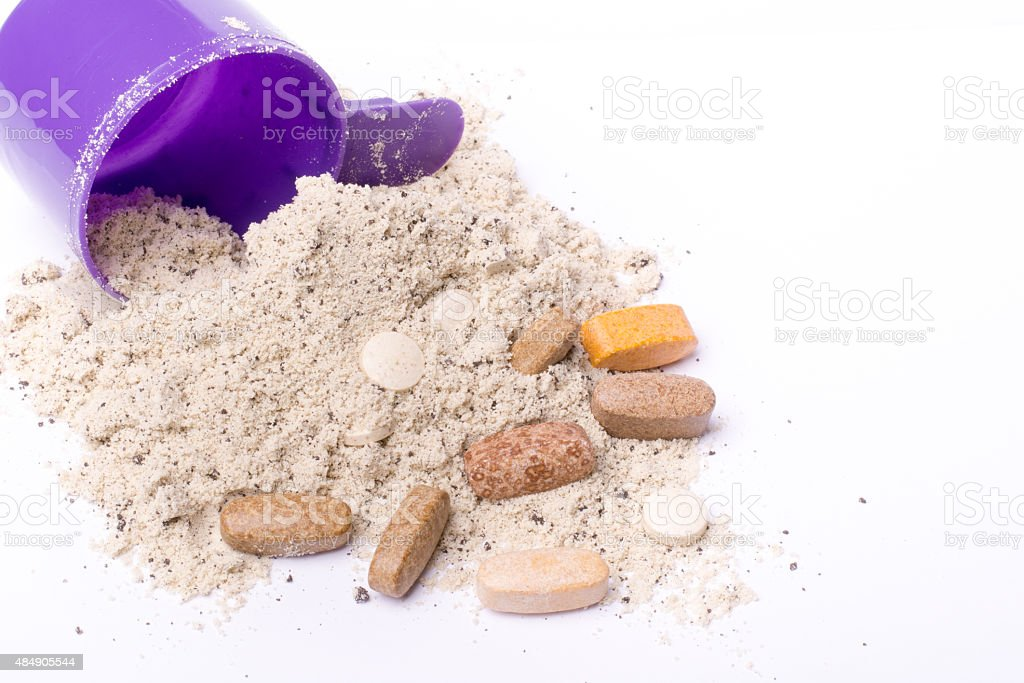 Whey protein powder in scoop with vitamins and plastic shaker stock photo