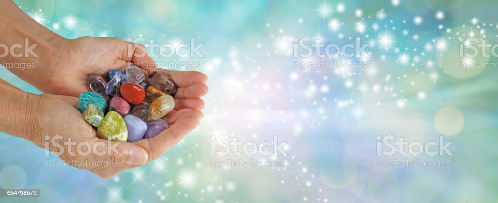 Which stone attracts you - Crystal Therapist offering a handful of crystals stock photo