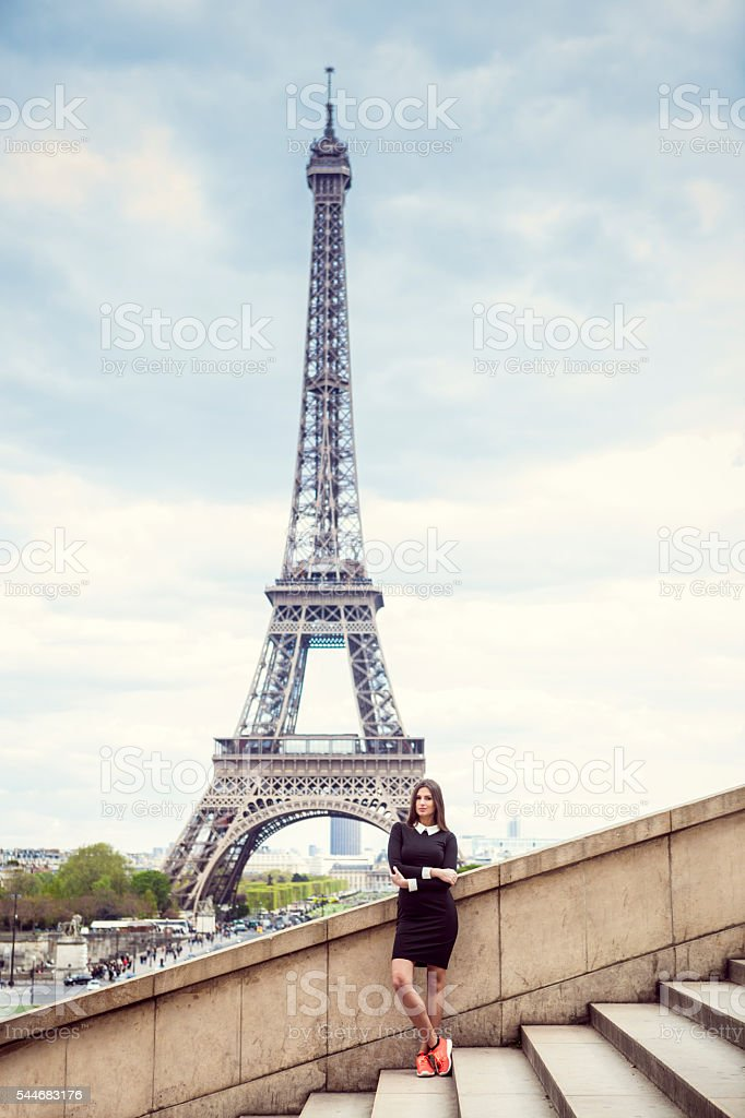 Young woman in trendy clothing is standing on the stairs where the...