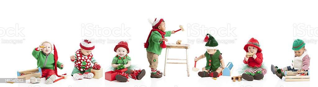 Whimsical Christmas Elves Helper Babies Make Toys in Santas Work stock photo
