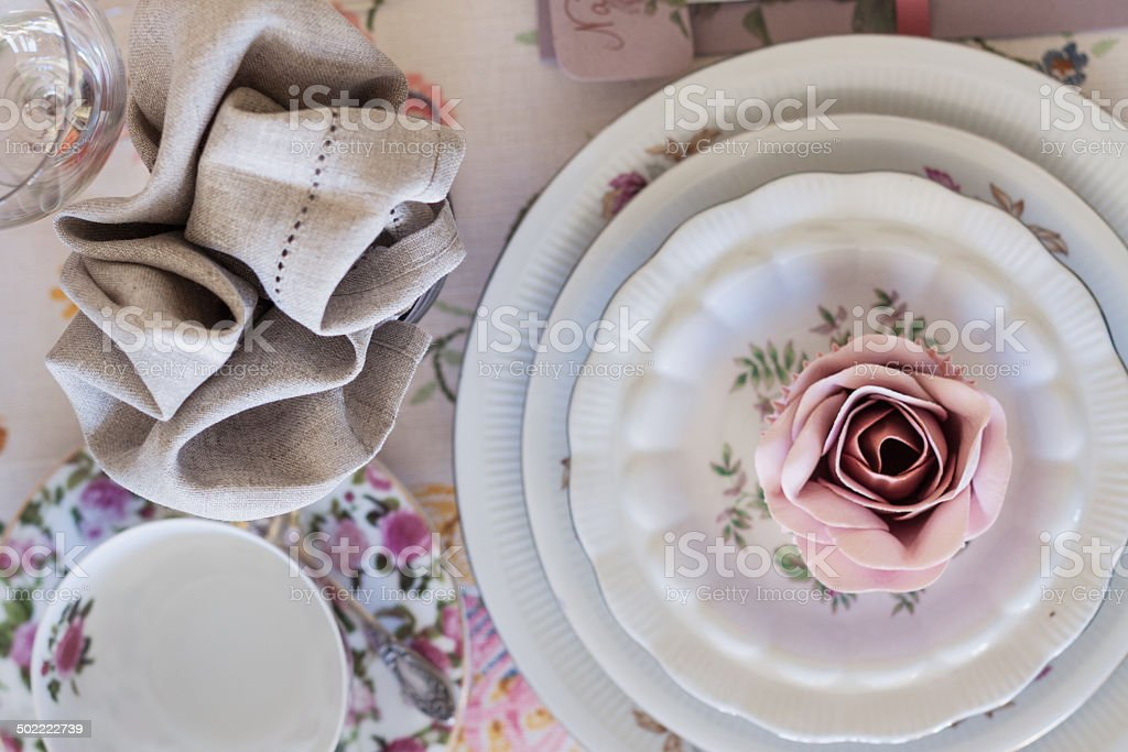 Whimsical place setting with sugar rose cupcake on vintage china. stock photo