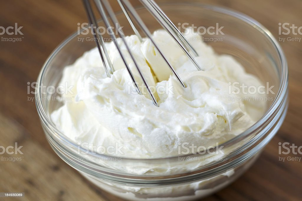Whipped cream and whisk in glass bowl stock photo