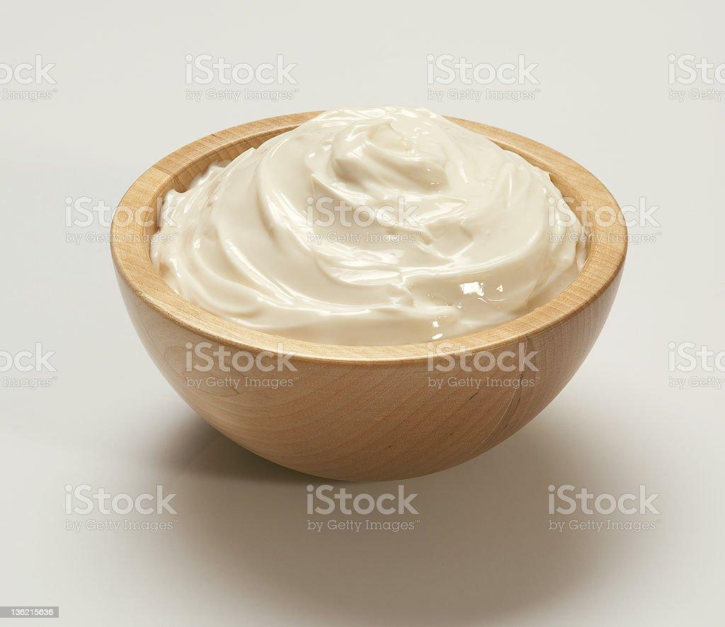Whipped cream in light wooden bowl on white backing stock photo