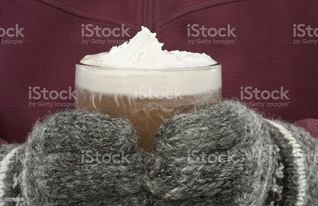 Whipped cream topped hot chocolate being held by gloved hands-close-up royalty-free stock photo