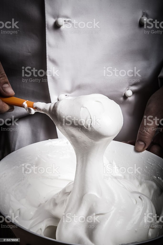 Whipped egg whites for pastry in a white ceramic bowl stock photo