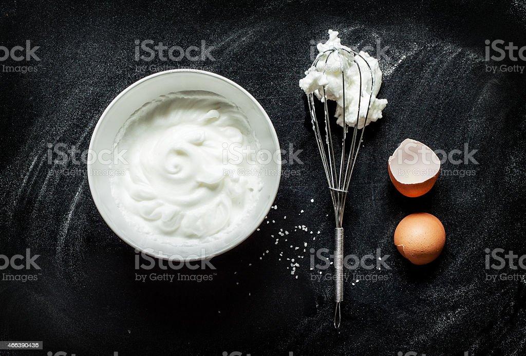 Whipped egg whites into a foam on black chalkboard stock photo