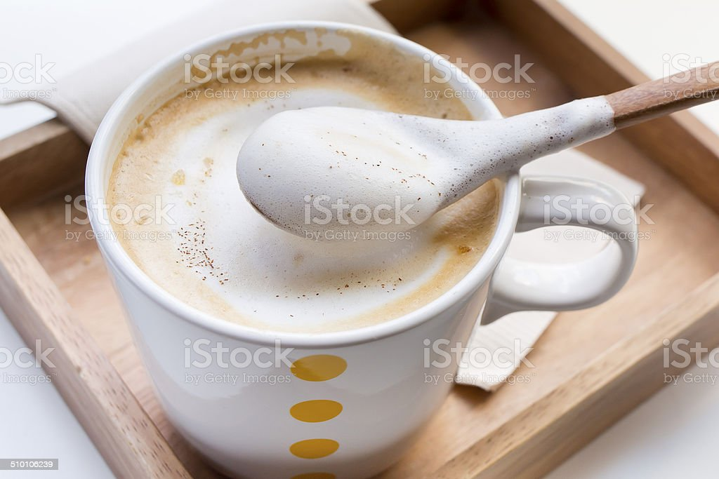 Whipping Cream on a spoon and a cup of coffee Cappuccino stock photo