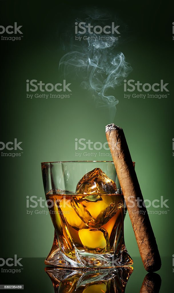 Whiskey and cigar on green stock photo