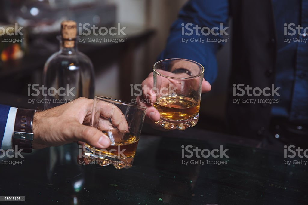 Whiskey glass in a hand of two mans stock photo