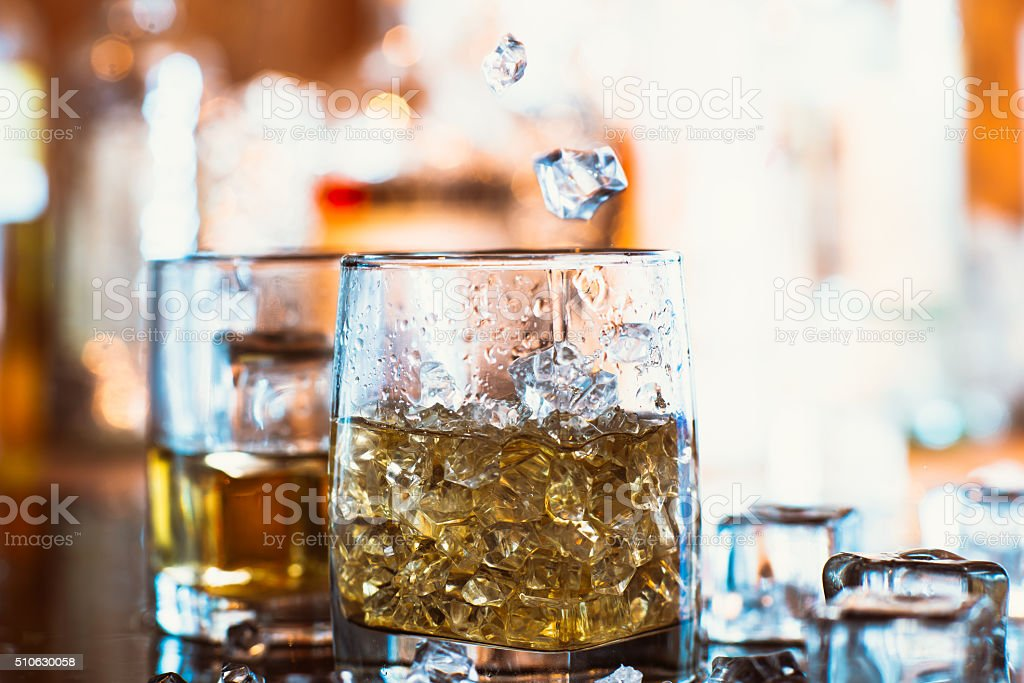 whiskey glass with ice and warm light on black table stock photo