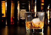 whiskey glass with ice in front of bottles