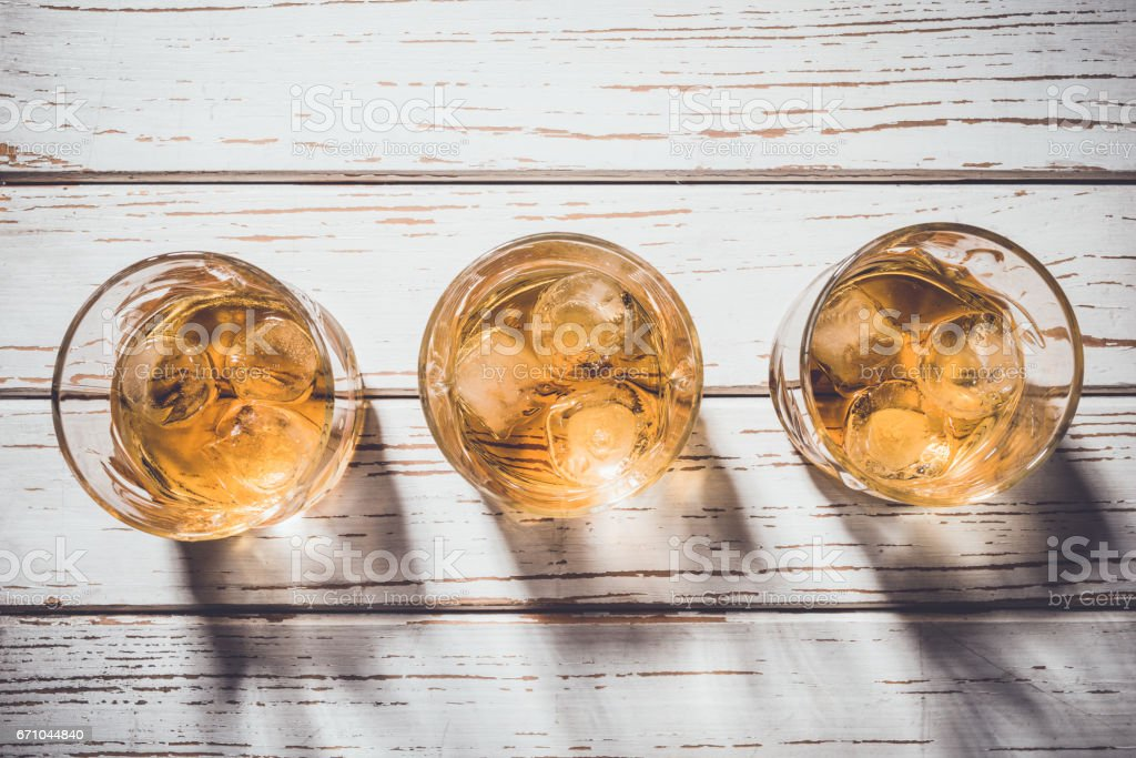 Whiskey glasses with ice cubes on an old wooden table stock photo