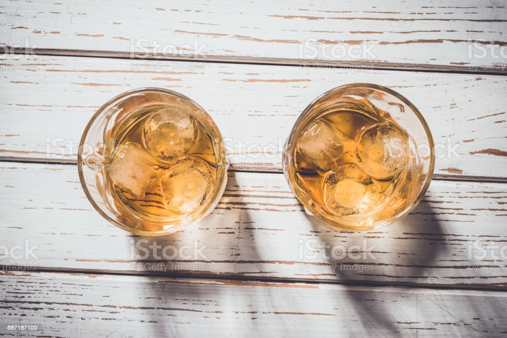 Whiskey glasses with ice cubes on white wooden table stock photo