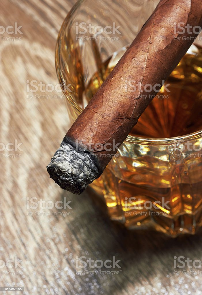 Whiskey in crystal glass with burning cigar on top royalty-free stock photo