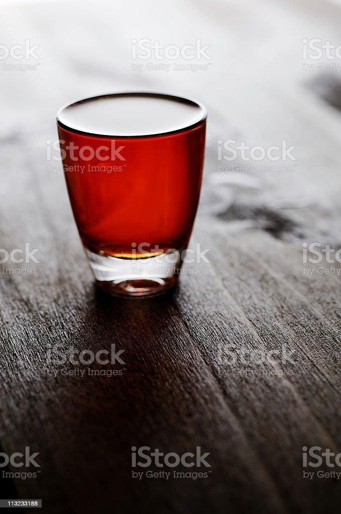 whiskey, scotch, bourbon shot glass back lit against dark oak royalty-free stock photo
