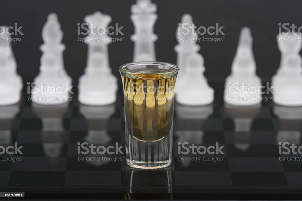 Whiskey shot in front of chess pieces royalty-free stock photo