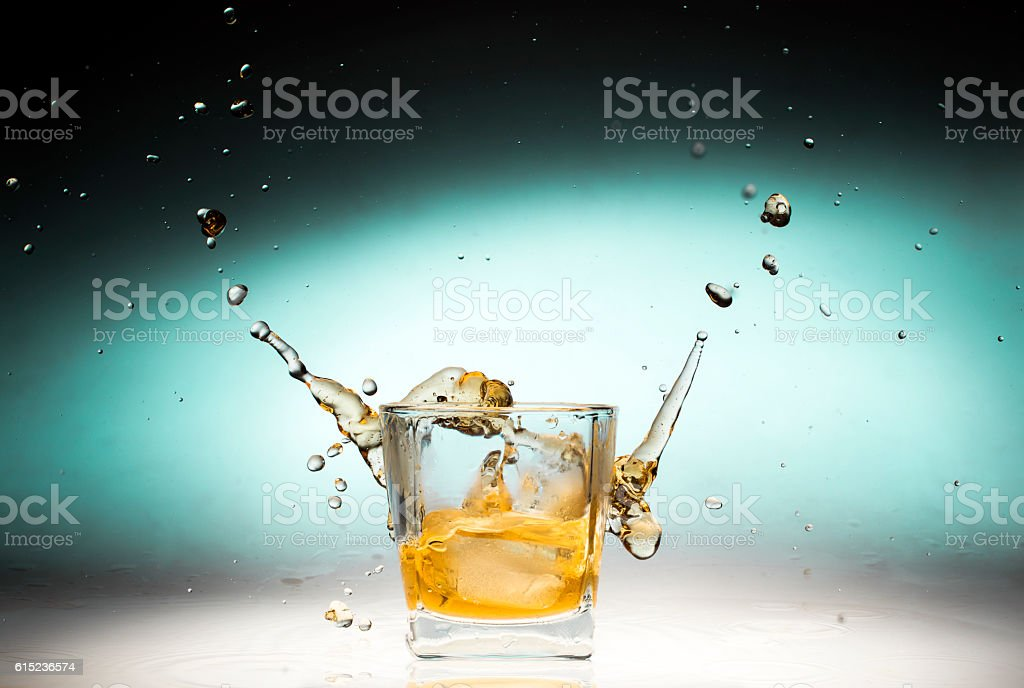 Whiskey shot splashing out of glass stock photo